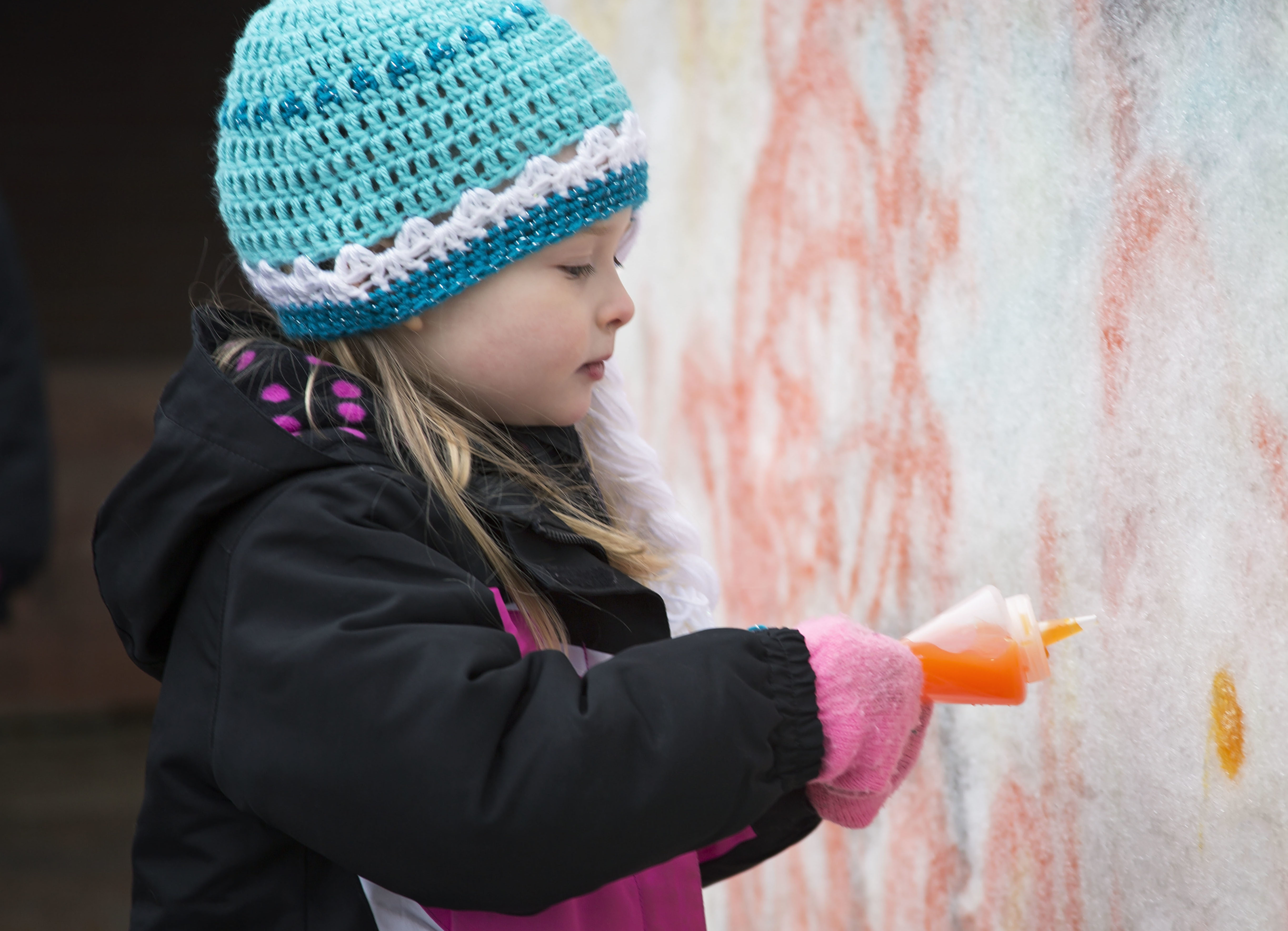 Child painting on snow sculpture